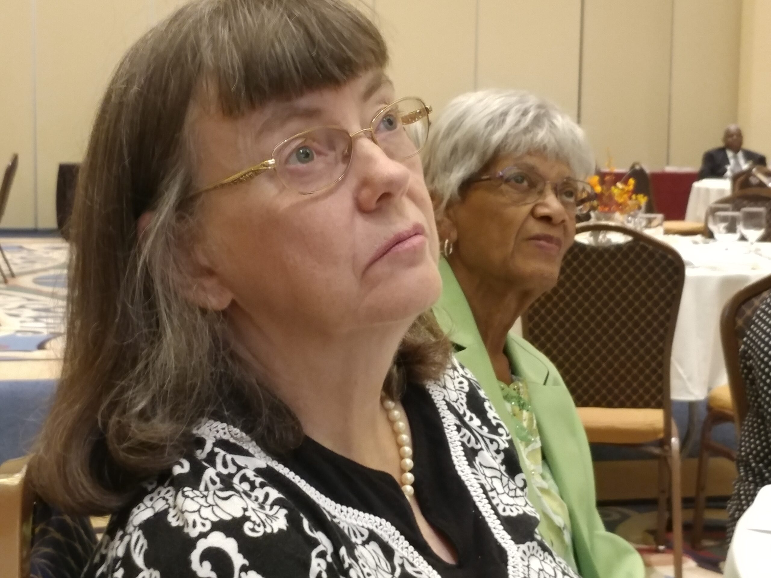 Two older women sitting at an event, paying attention to the event speaker.