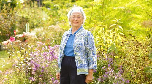An older Caucasian woman standing in the fields with trees and plants.