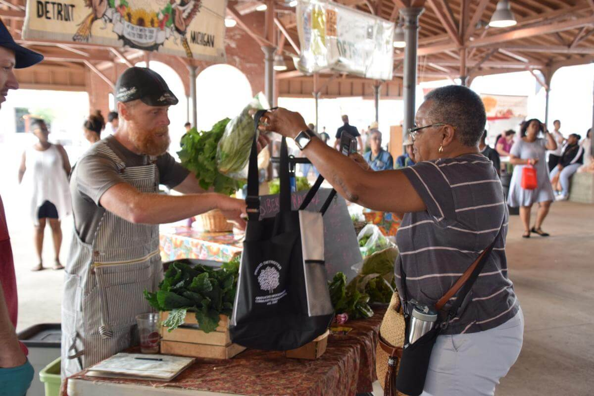 A man holding a bag up for a woman who is adding vegetables to her bag. | Long-Term Care Ombudsman Program