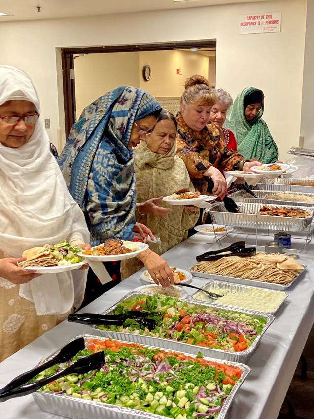 A group of women getting mediterranean food down an assembly line.