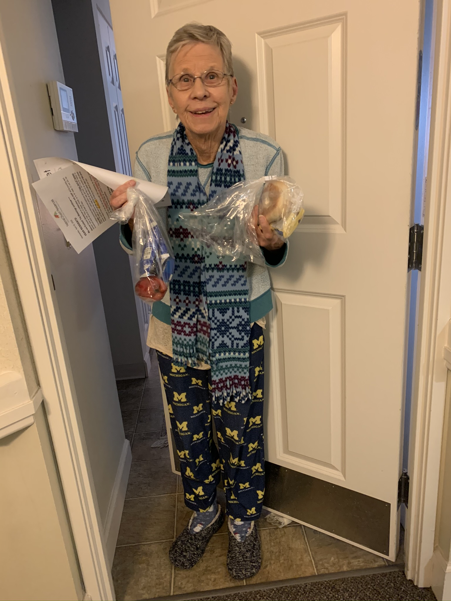 An older woman standing in front of her door holding papers and a bag with food