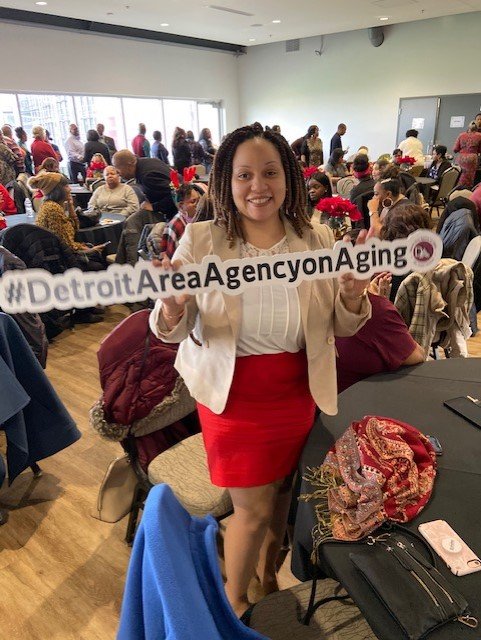 A woman standing at an event holding a Detroit Area Agency on Aging sign | Quality and Compliance landing page