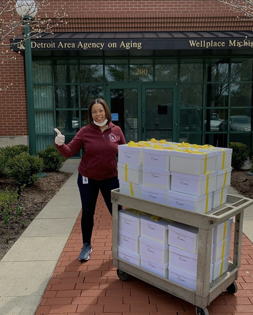 Detroit Area Agency on Aging staff member standing outside with a cart full of boxes.