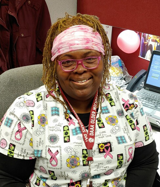 An African-American woman wearing scrubs is sitting at a desk, smiling at the camera.