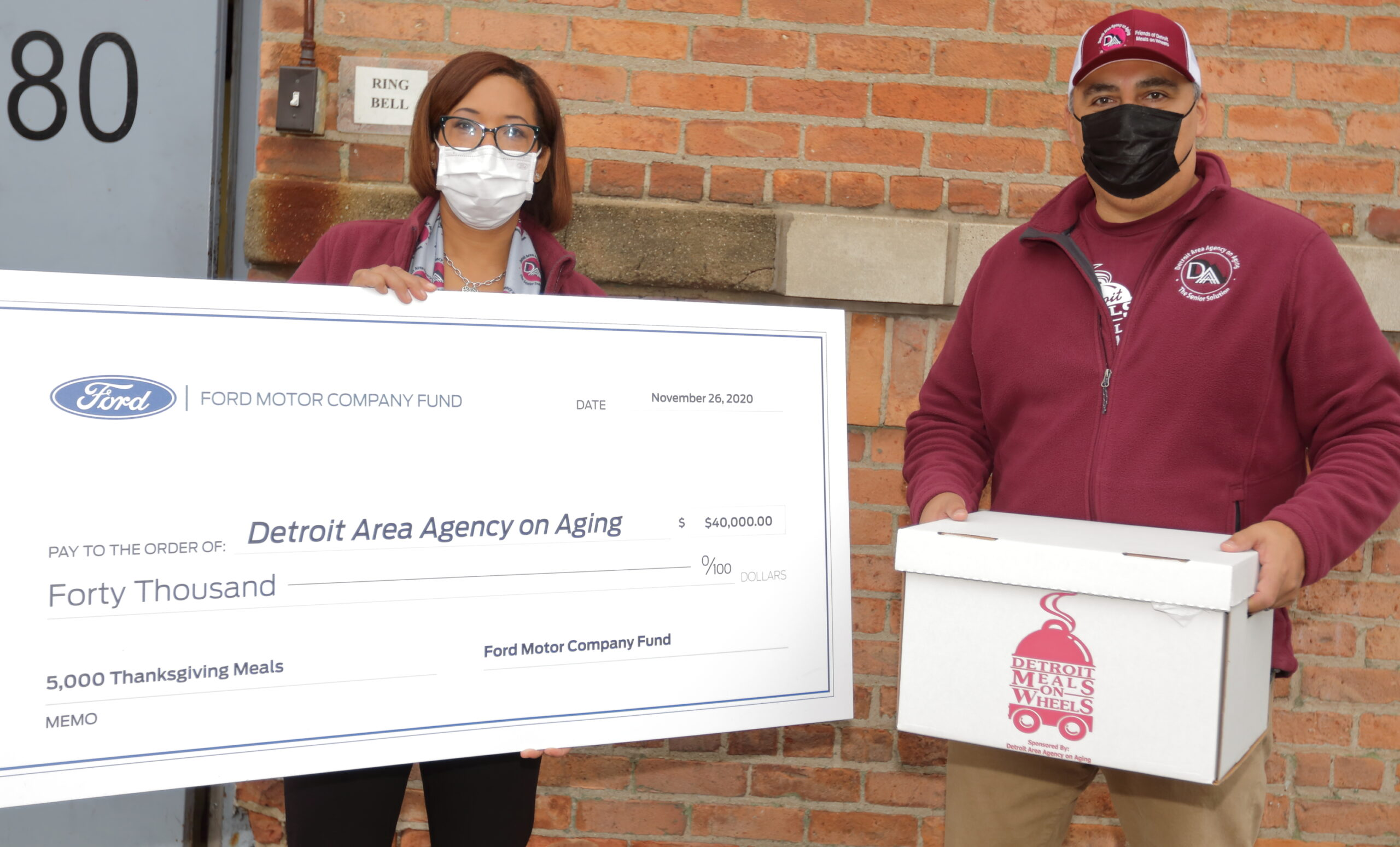 A woman and man standing outside wearing masks while the woman is holding a large check from Ford Motor Company and the man holding a box.