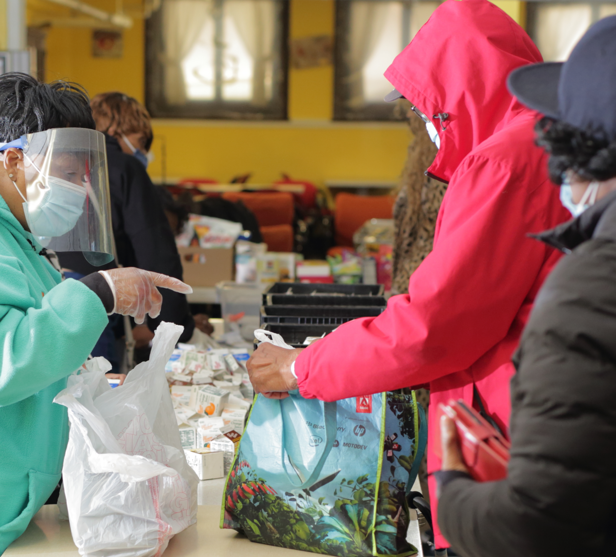 Individuals getting food to fill their reusable bags and DAAA volunteers helping to give out items   Image of a DAAA volunteer scooping food with their protective gloves and masks on   DAAA's Congregate Meal Program