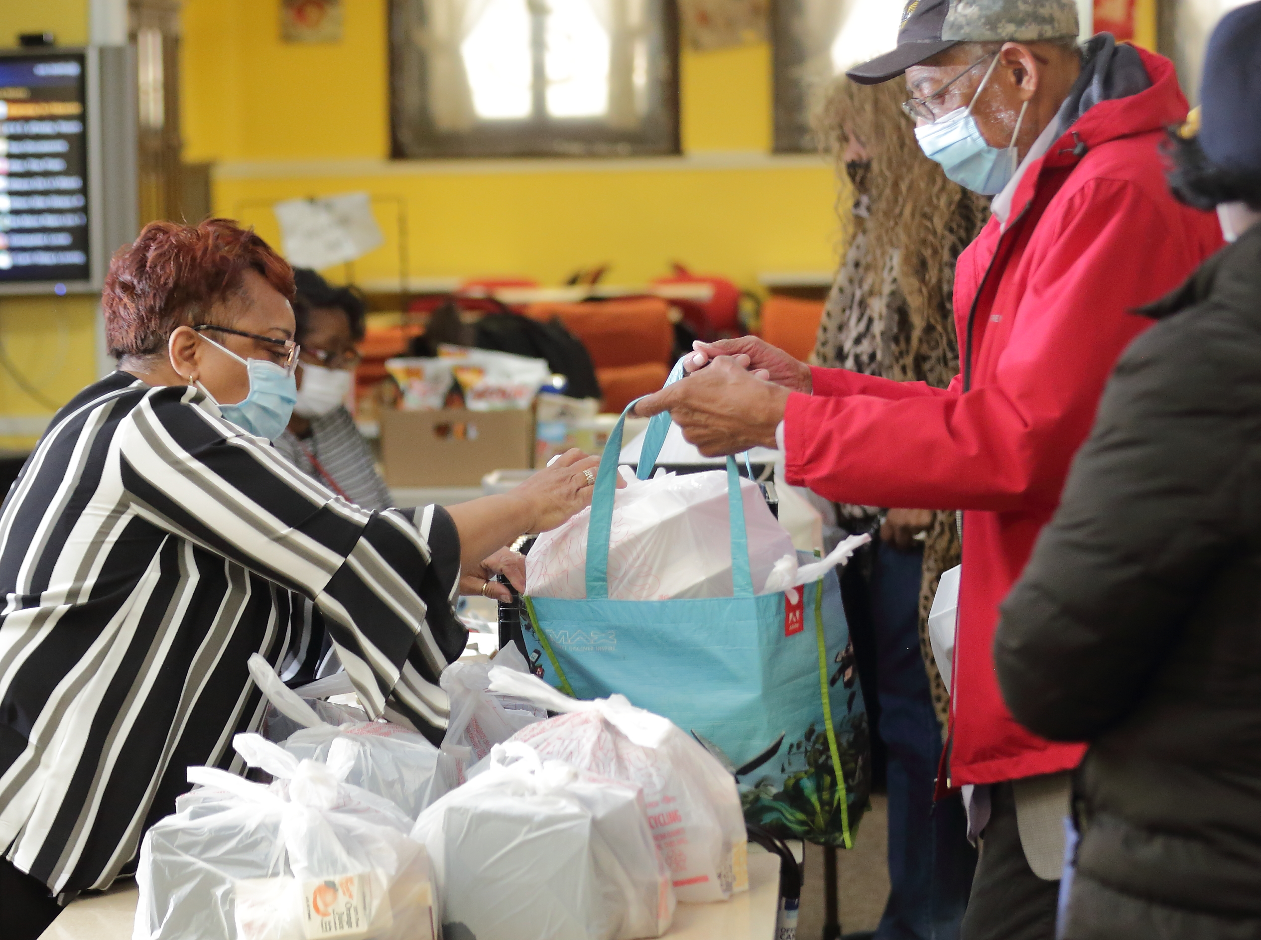 A woman is helping a man placing food carryouts in his reusable bag