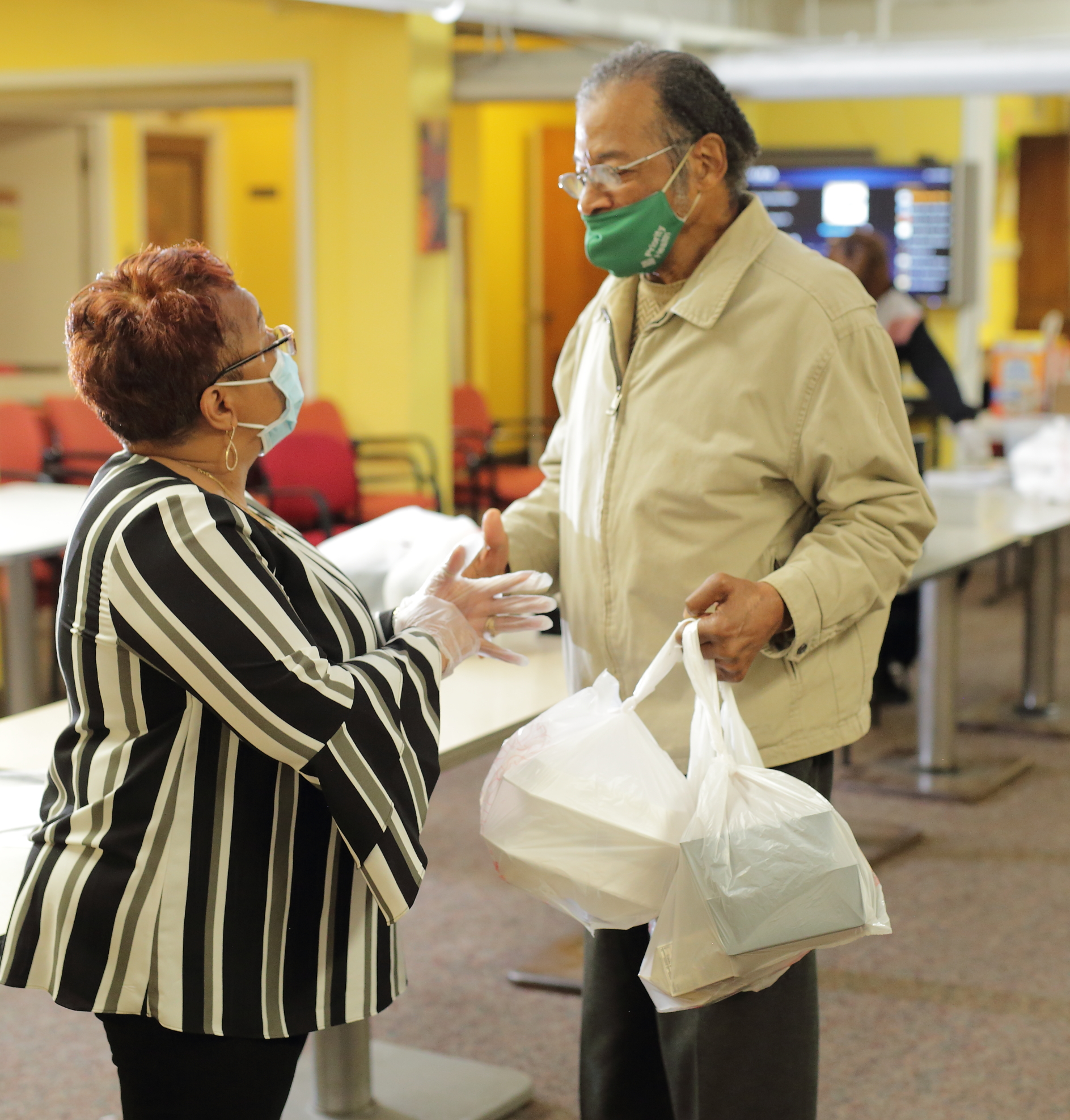 A woman talking to a man who is carrying multiple bags with food carryout containers