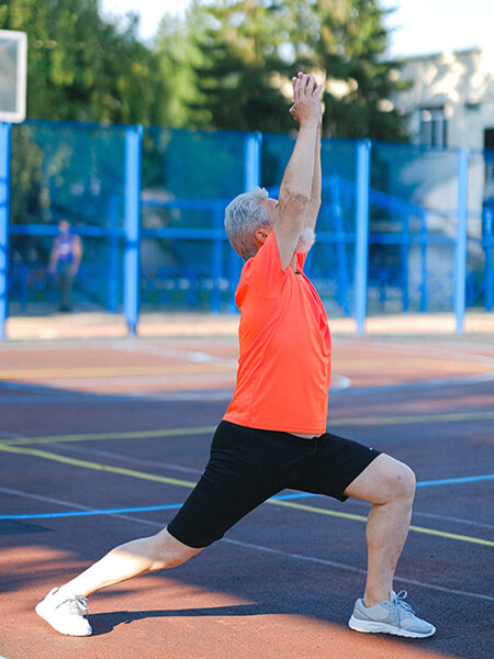 A man in an orange shirt stretching on the tennis court.